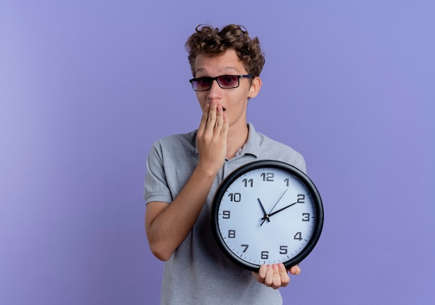 Jonge man in zwarte bril, gekleed in grijs poloshirt met wandklok op zoek verrast en verbaasd staande over blauwe muur