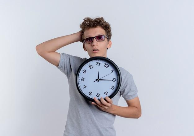 Jonge man in zwarte bril, gekleed in grijs poloshirt met wandklok verward met hand op zijn hoofd staande over witte muur