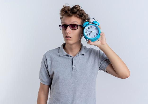 Jonge man in zwarte bril, gekleed in grijs poloshirt met wekker in de buurt van zijn gezicht op zoek bezorgd over wit