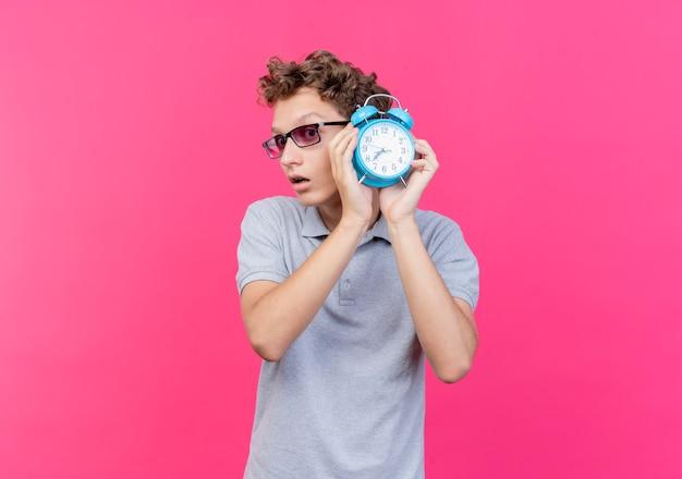 Jonge man in zwarte bril, gekleed in grijs poloshirt met wekker opzij kijken bezorgd staande over roze muur
