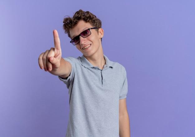 Jonge man in zwarte bril, gekleed in grijs poloshirt met wijsvinger lachend met blij gezicht staande over blauwe muur