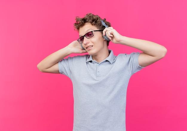 Jonge man in zwarte bril met grijs poloshirt met koptelefoon glimlachend vrolijk genietend van favoriete muziek staande over roze muur