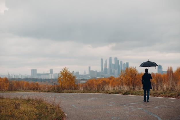 Jonge man in zwarte jas lopen naar de stad in de regen met paraplu