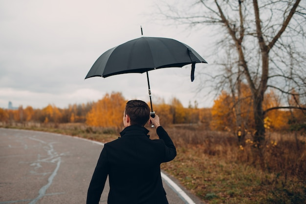 Jonge man in zwarte jas wandelen in de regen met paraplu