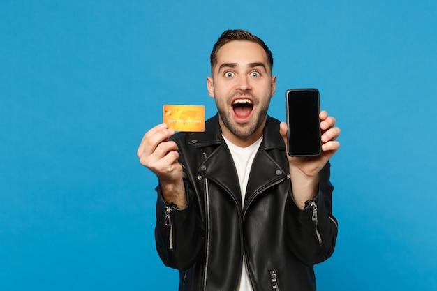 Jonge man in zwarte jas wit t-shirt houdt mobiele telefoon leeg scherm voor promotionele inhoud creditcard geïsoleerd op blauwe muur achtergrond studio portret. mensen levensstijl concept mock up kopie ruimte