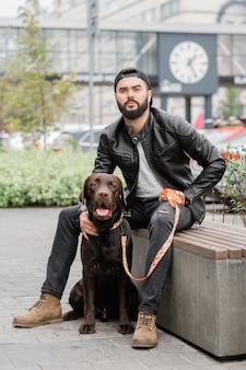 Jonge man in zwarte jeans en leren jas zittend op de bank met hond
