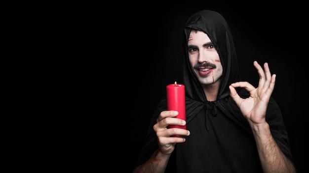 Jonge man in zwarte mantel met kaars ok gebaar maken