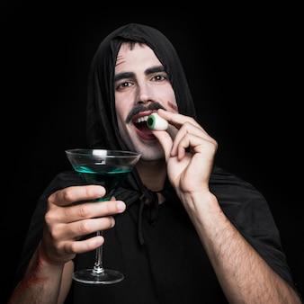 Jonge man in zwarte mantel poseren in studio met kunstmatige ogen en drank
