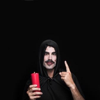Jonge man in zwarte mantel staande in studio met kaars