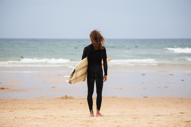 Jonge man in zwarte wetsuit op het strand met surfplank overdag