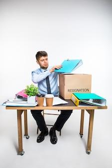 Jonge man is berustend en vouwt dingen op de werkplek, mappen, documenten.