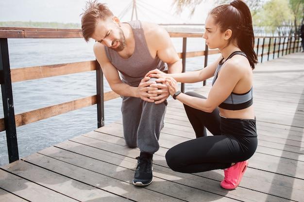 Jonge man is op de brug met zijn vriendin. hij heeft pijn in zijn knie.