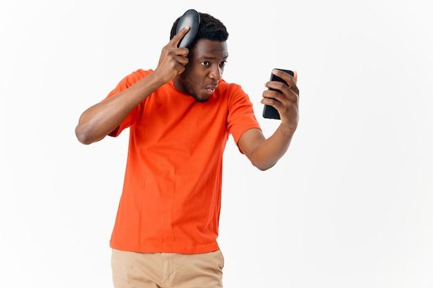 Jonge man kamt zijn haar terwijl hij naar de telefoon kijkt