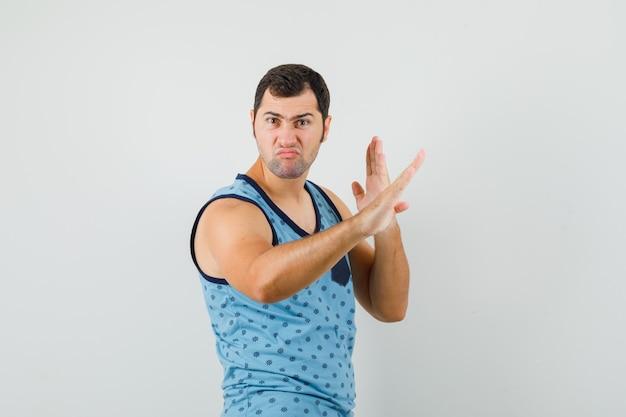 Jonge man karate hakken gebaar in blauwe hemd tonen en op zoek zelfverzekerd. vooraanzicht.