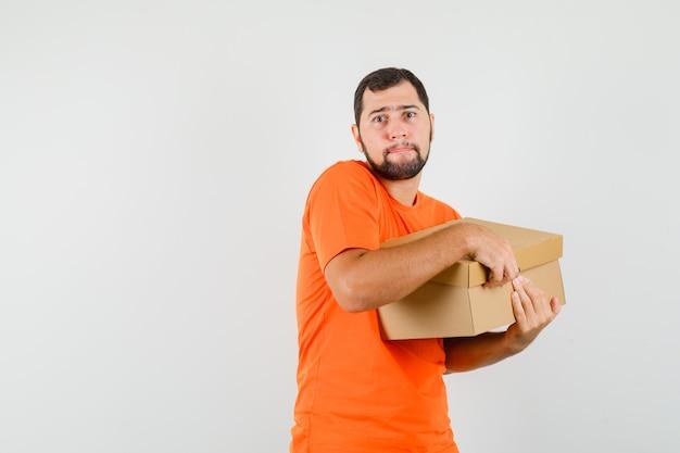 Jonge man kartonnen doos openen in oranje t-shirt en op zoek naar ernstige, vooraanzicht.