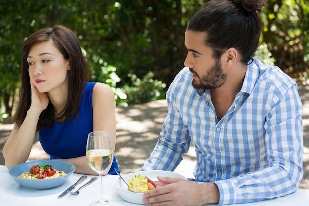 Jonge man kijken boos vrouw in openluchtrestaurant