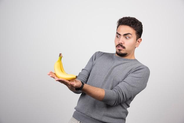Jonge man kijkend naar banaan op grijs.