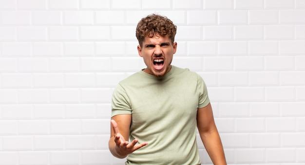 Jonge man kijkt boos, geïrriteerd en gefrustreerd schreeuwend wtf of wat is er mis met je
