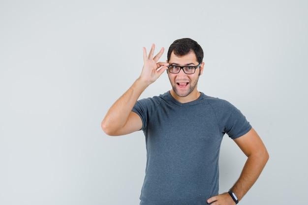 Jonge man kijkt door een bril in grijs t-shirt en ziet er intelligent uit