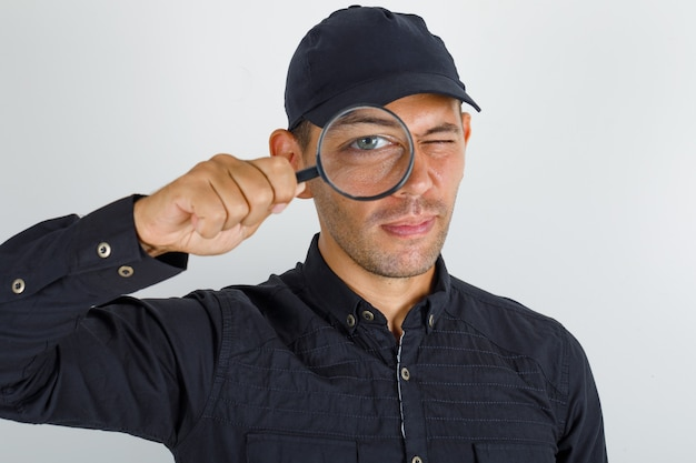 Jonge man kijkt door vergrootglas in zwart shirt met pet