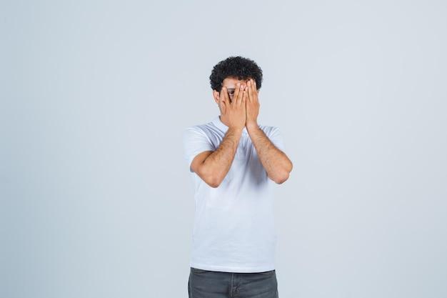 Jonge man kijkt door vingers in wit t-shirt, broek en ziet er bang uit, vooraanzicht.