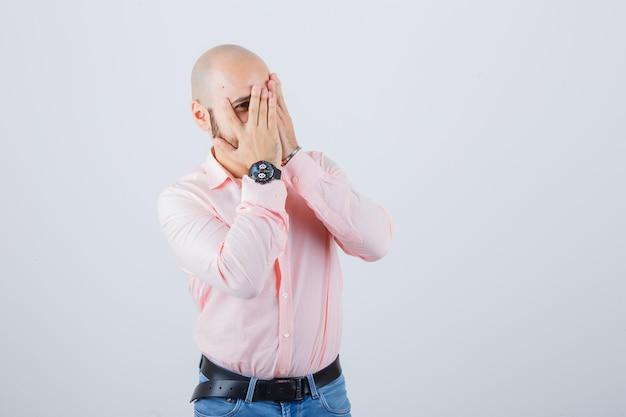 Jonge man kijkt door vingers met één oog in shirt, spijkerbroek en ziet er schattig uit, vooraanzicht.