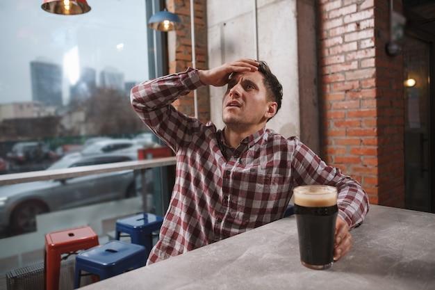 Jonge man kijkt er kapot van, kijkt naar wedstrijd op het scherm in biercafé
