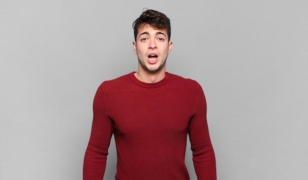 Jonge man kijkt erg geschokt of verrast, starend met open mond en zegt wow