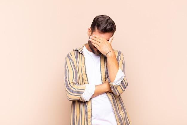 Jonge man kijkt gestrest, beschaamd of boos, met hoofdpijn, gezicht bedekt met hand