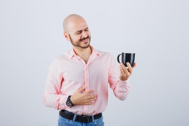 Jonge man kijkt naar beker in roze shirt, spijkerbroek en ziet er optimistisch uit. vooraanzicht.