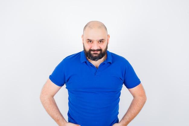 Jonge man kijkt naar camera in blauw shirt en kijkt geconcentreerd. vooraanzicht.