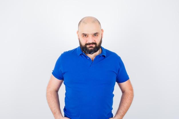Jonge man kijkt naar camera in blauw shirt en ziet er kalm uit, vooraanzicht.