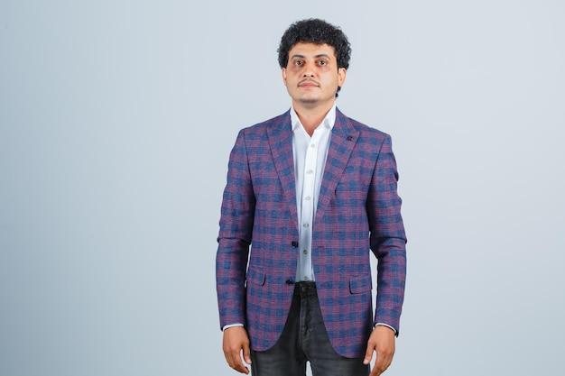 Jonge man kijkt naar camera in shirt, jas, broek en ziet er knap uit, vooraanzicht.