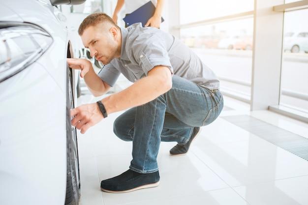 Jonge man kijkt naar de ruimte tussen de carrosserie en het wiel
