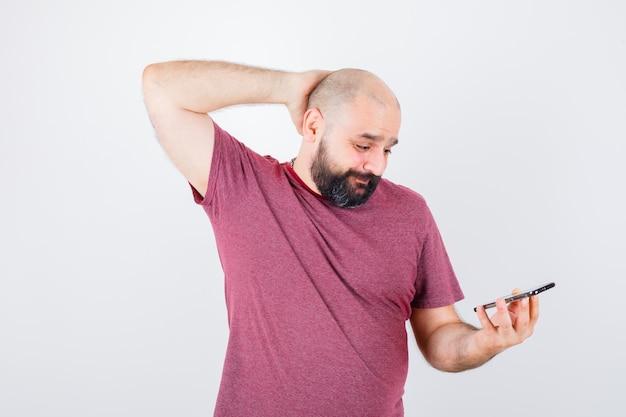 Jonge man kijkt naar de telefoon en legt de hand op het hoofd in een roze t-shirt en kijkt geïrriteerd, vooraanzicht.