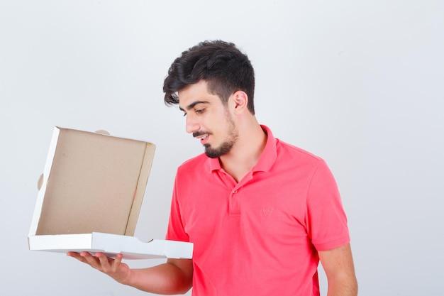 Jonge man kijkt naar geopende pizzadoos in t-shirt en kijkt aarzelend. vooraanzicht.