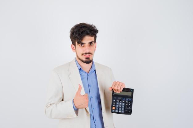Jonge man kijkt naar rekenmachine en toont duim in blauw shirt en wit jasje en ziet er gelukkig uit