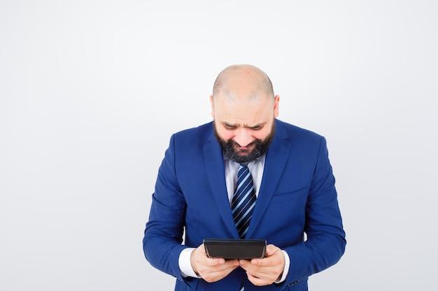 Jonge man kijkt naar rekenmachine in wit overhemd, jas en kijkt weemoedig, vooraanzicht.