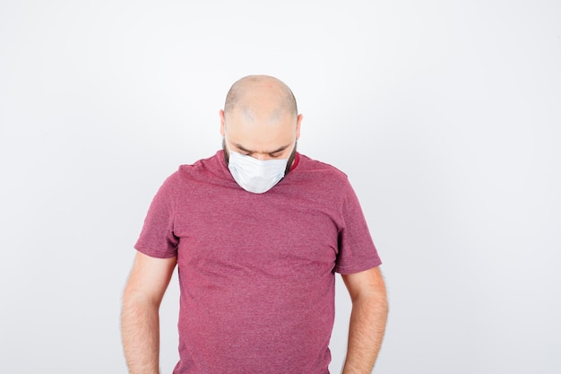 Jonge man kijkt neer in roze t-shirt, masker en ziet er treurig uit. vooraanzicht.
