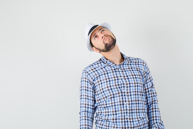 Jonge man kijkt omhoog in geruit overhemd, hoed en kijkt gericht. vooraanzicht.