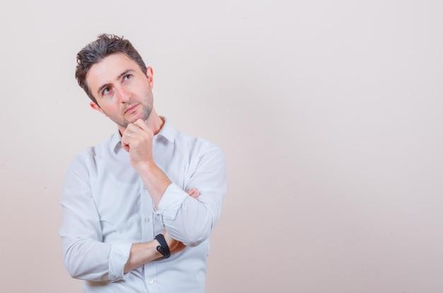 Jonge man kijkt omhoog terwijl hij zijn kin in een wit overhemd houdt en peinzend kijkt looking
