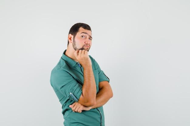 Jonge man kijkt opzij in groen shirt en kijkt geïnteresseerd, vooraanzicht.