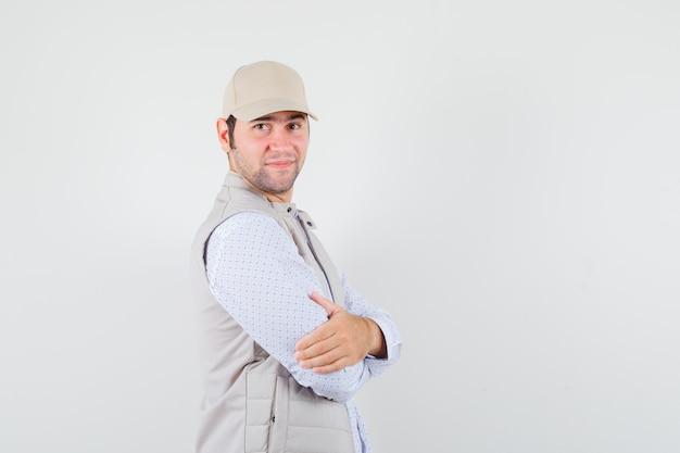 Jonge man kijkt opzij in shirt, mouwloos jasje, pet en kijkt tevreden.