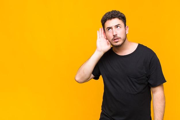 Jonge man kijkt serieus en nieuwsgierig, luistert, probeert een geheim gesprek of roddelen te horen, afluistert