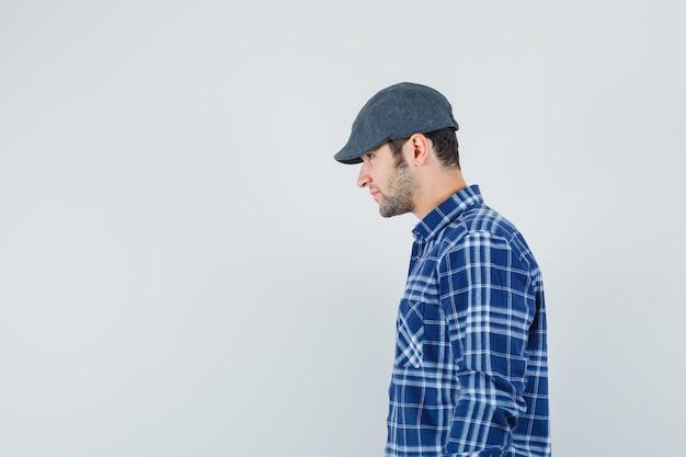 Jonge man kijkt uit in blauw shirt, pet. vrije ruimte voor uw tekst