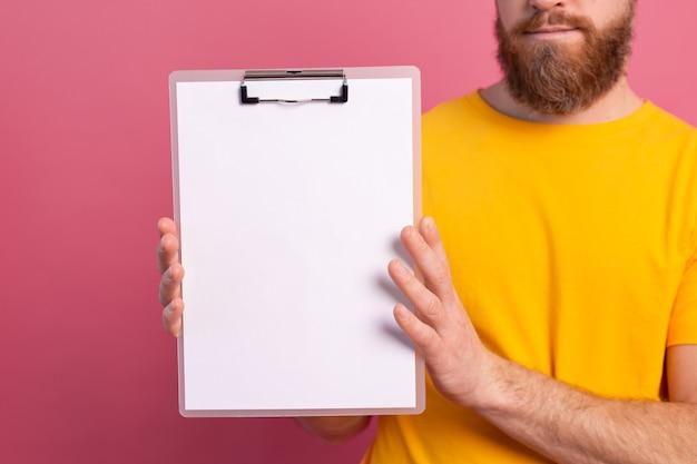 Jonge man kijkt uit ogen wit leeg leeg reclamebord voor promotionele inhoud geïsoleerd studio-opname