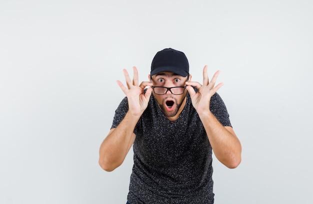 Jonge man kijkt uit over bril in t-shirt en pet en kijkt geschokt