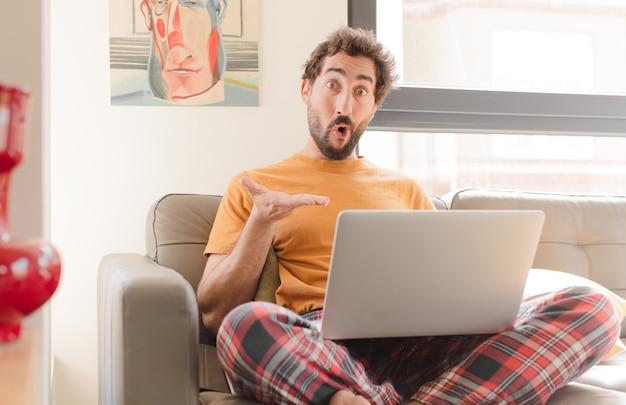 Jonge man kijkt verbaasd en geschokt met open mond en houdt een voorwerp vast met een open hand aan de zijkant