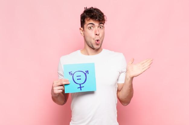 Jonge man kijkt verbaasd en geschokt, met open mond naar beneden terwijl hij een voorwerp vasthoudt met een open hand op de zijkant