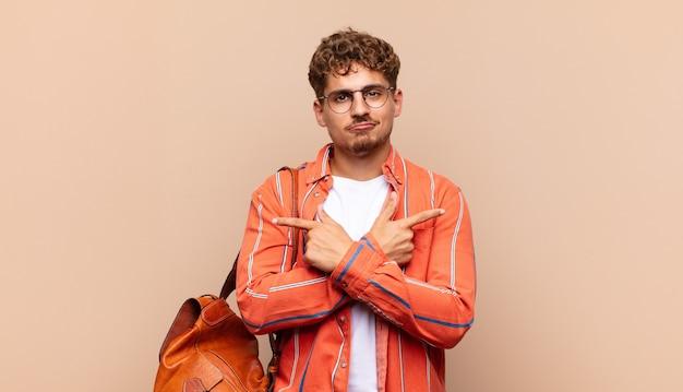 Jonge man kijkt verbaasd en verward, onzeker en wijst in tegengestelde richting met twijfels